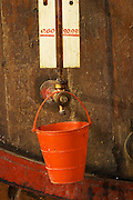 Children's toy bucket to avoid wine dripping. Chateau de Nouvelles. Fitou. Languedoc. Barrel cellar. Wooden fermentation and storage tanks. Tank spout. France. Europe.