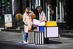 "© Licensed to London News Pictures. 14/09/2019. LONDON, UK.  Tourists sit on a sculptural bench as ""Walala Lounge"" opens in Mayfair's South Molton Street.  Artist and designer Camille Walala's installation comprises 10 sculptural benches, accompanied by planters and a series of oversized flags strung, bunting-style, from shopfront to shopfront, converting the street into an immersive corridor of colour as part of this year's London Design Festival.  Photo credit: Stephen Chung/LNP"