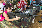 """11 JANUARY 2014 - BANGKOK, THAILAND:  A Thai girl plays with a TAVOR Assault Rifle during Children's Day in Bangkok. The Royal Thai Army hosted a """"Children's Day"""" event at the 2nd Cavalry King's Guard Division base in Bangkok. Children had an opportunity to look at military weapons, climb around on tanks, artillery pieces and helicopters and look at battlefield medical facilities. The Children's Day fair comes amidst political strife and concerns of a possible coup in Thailand. Earlier in the week, the Thai army announced that movements of armored vehicles through Bangkok were not in preparation of a coup, but were moving equipment into position for Children's Day.     PHOTO BY JACK KURTZ"""