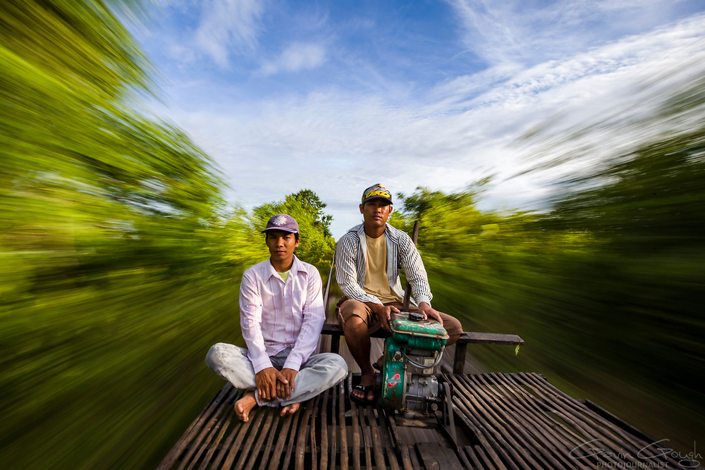 Two drivers of bamboo train, or Norry, speed along a railway track, O Dambong, Battambang, Cambodia
