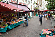 Shoppers walk through the market on the Rue Mouffetard.<br /> Rue Mouffetard is in the Fifth (cinquieme) arrondisement and the street is very old: originally a Roman rod running from the Roman Rive Gauche city south the Italy. The market is famous for it's quality fresh produce and artisanal food shops.