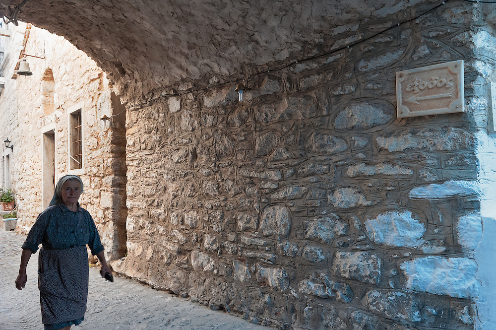 A local woman walks under an arch in in Mesta village in Chios island, Greece.