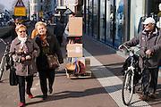 In Utrecht loopt een transporteur met Jura koffiezetapparaten op een steekwagen langs twee oudere dames die gearmd lopen en een allochtone man met een fiets in de binnenstad.<br /> <br /> In Utrecht, a conveyor with Jura coffee machines running on a trolley walks along two older ladies who walk arm in arm and an immigrant man with a bike in the city center.