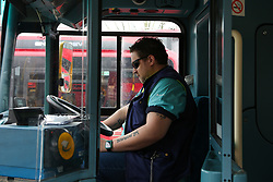 © Licensed to London News Pictures. 23/03/2021. London, UK. A bus driver observes a minute's silence on a bus at Turnpike Lane Bus Station in north London to remember the over 126,000 people who have died from Covid-19, and the many more lives that have been impacted. A total of 88 London transport workers have died in the pandemic, 51 of them bus drivers. Photo credit: Dinendra Haria/LNP