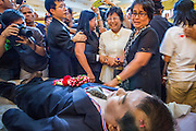 27 JANUARY 2014 - BANGKOK, THAILAND: Anti-government activists react to seeing the body of Suthin Taratin, their leader, during bathing rites for Suthin at Wat Sommanat Rajavaravihara in Bangkok. In Thai tradition, after death a bathing ceremony takes place in which relatives and friends pour water over one hand of the deceased. Suthin was a core leader of the People's Democratic Force to Overthrow Thaksinism (Pefot), one of several organizations leading protests against the elected government of Thai Prime Minister Yingluck Shinawatra. He was murdered Sunday, Jan. 28, while he was leading a rally to prevent voters from reaching a polling center in the Bang Na district of Bangkok.     PHOTO BY JACK KURTZ