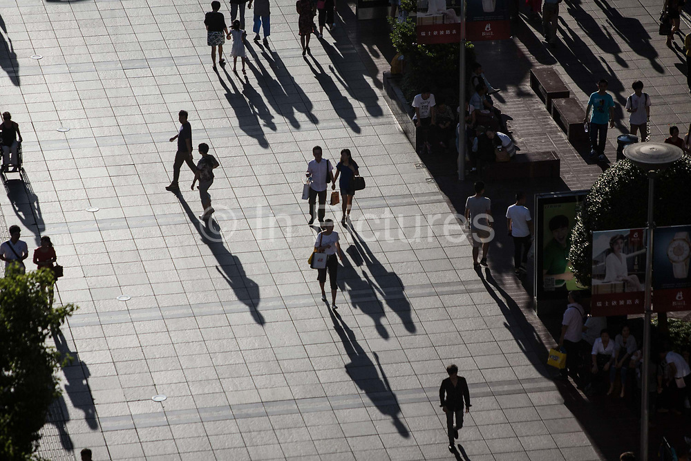 Shoppers walk on the Nanjing East Road pedestrian street in Shanghai, China, on Sept. 28, 2015.