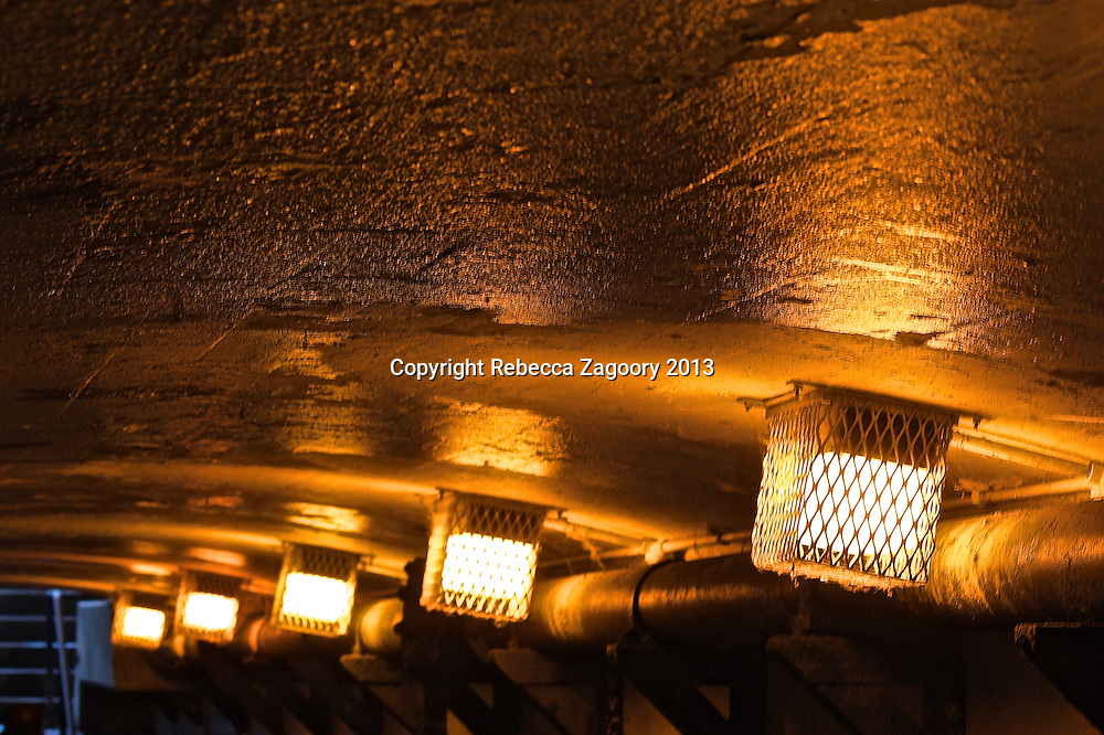 Inside a commuter's passageway, white lights against an aged and abandoned ceiling the gold hue illuminates the texture within.