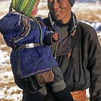 MONGOLIA, Darhad Valley. Ganshishgen with her herding father, Ganzarig, after a long day's ride during their migration to Lake Hovsgol.