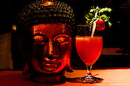 A bloody mary cocktail stands next to a buddha head at Club L'Oriental, Hanoi, Vietnam