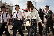 Foreign tourists and commuters walk southwards over London Bridge, from the City of London - the capital's financial district founded by the Romans in the 1st century - to Southwark on the south bank, on 6th August 2018, in London, England.