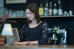 Young waitress using computer in coffee shop at checkout counter, Freiburg Im Breisgau, Baden-W¸rttemberg, Germany