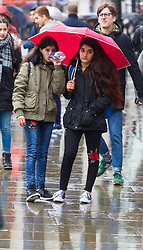 Two girls share a red umbrella at Piccadilly Circus. As forecasters predicted, the rain arrives in London where Londoners and tourists go about their business. London, February 13 2018.