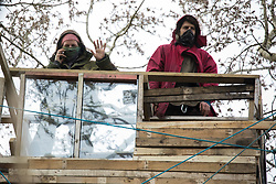 Steeple Claydon, UK. 23 February, 2021. Anti-HS2 activists observe National Eviction Team bailiffs from a tree house during an operation by HS2 Ltd to evict activists living in ancient woodland known as Poors Piece. The activists created the Poors Piece Conservation Project there in spring 2020 after having been invited to stay on the land by its owner, farmer Clive Higgins. Already, local village communities have been hugely impacted by HS2, with 550 acres of land seized including a large section of a nature reserve.