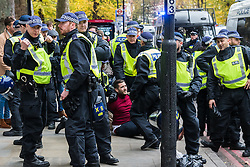 London, November 6th 2016. A man arrested by police sits on the pavement in Islington following a scuffle after the North London Derby between Arsenal FC and Tottenham Hotspur, that ended in a 1-1 draw.