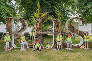 Children from the Toad Hall Nursery with the RHS sign - The Hampton Court Flower Show, organised by the Royal Horticultural Society (RHS). In the grounds of the Hampton Court Palace, London.