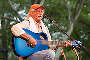 Arlo Guthrie playing a blue Legacy Composite Acoustic guitar.