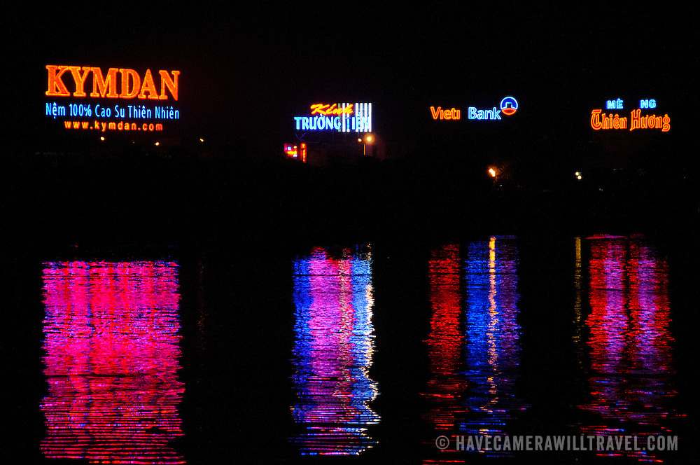 Lights from the illuminated neon advertising signs on the Perfume River are reflected at night on the river surface.