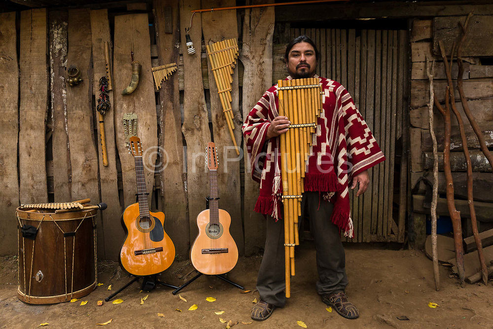 Musician Jose Otaiza, 43 in front of his ancestral homes entrance, 20 Kms outside Villarica town. José grew up in the poorist neighbourhood on the outskirts of Santiago. Hes a mestizo, mother being a Mapuche, father is a white Chilean. José quit schooling at an early age, to dedicate himself to music and became a street musician. He then joined a group and began touring, particularly in Argentina. He then followed his ambition and traveled across Latin America, mainly Peru, Bolivia and Ecuador to further his knowledge of Indigenous musical expressions. Following on he traveled to Europe, principally Germany  for several years before returning to reconnect with his  Mapuche  heritage which he strongly missed. Seen here with his collections of instruments which he plays and makes. Loncoche, Chile. February 9, 2018.