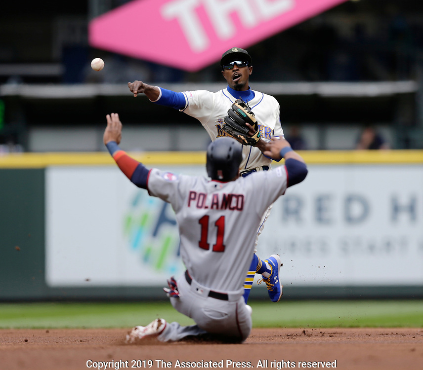 Minnesota Twins' Jorge Polanco is forced out at second as Seattle Mariners second baseman Dee Gordon makes a throw to first to complete a double play on Jonathan Schoop at first during the first inning of a baseball game, Sunday, May 19, 2019, in Seattle. (AP Photo/John Froschauer)