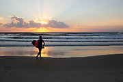 Silhouette of surfers on the beach of the Mediterranean sea. Photographed in Tel Aviv at sunset