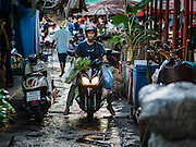 01 DECEMBER 2016 0 BANGKOK, THAILAND: A woman rides her motorcycle through the traditional market on Lan Luang Road in Bangkok. The market is on the site of one of the first western style cinemas in Bangkok. The movie theatre closed years ago and is still empty but the market fills the streets around the theatre.     PHOTO BY JACK KURTZ