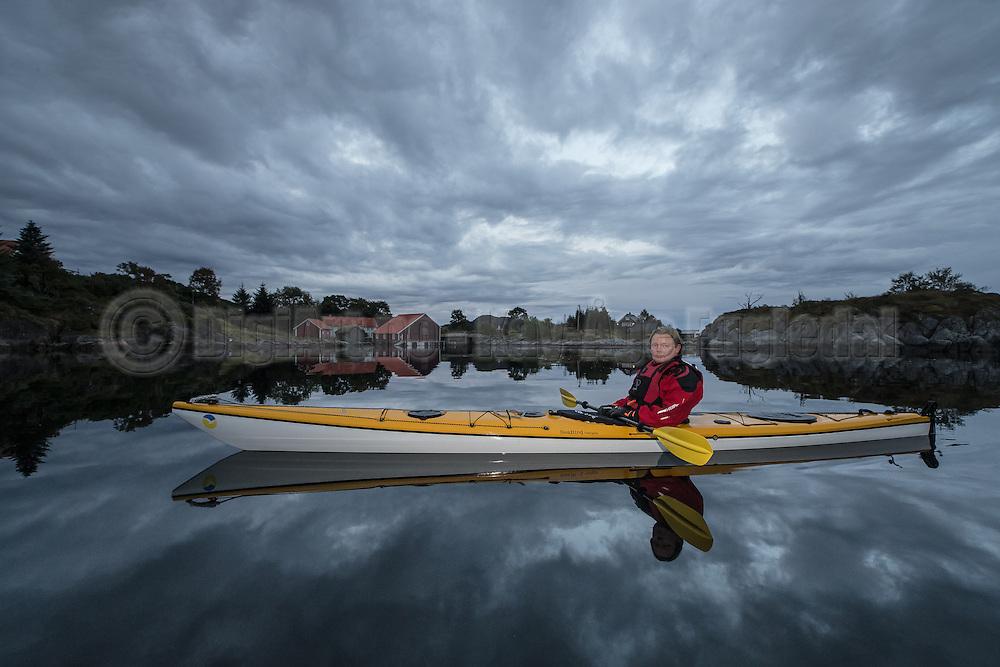 A Kayaker in nice environment with calm sea and nice sky. Approved by person for internet posting   Kajakkpadler i pent miljø med stille sjø og pen himmel. Godkjendt av person for internett.