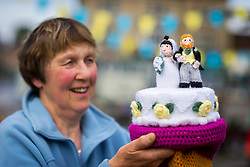 © Licensed to London News Pictures. 13/05/2018. Thirsk UK. Linda Miller of the Thirsk Yarn Bombers with her woollen creation of Prince Harry & Megan Markle. The Thirsk Yarn bombers have decorated the town centre of Thirsk in North Yorkshire this morning with Prince Harry & Megan Markle wedding related woollen creations to celebrate the upcoming royal wedding at the weekend. Photo credit: Andrew McCaren/LNP