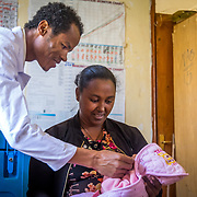 INDIVIDUAL(S) PHOTOGRAPHED: From left to right: Nega Alemneh, Embet Matebe, and Mariamawit Mikiyas. LOCATION: Mecha Health Center, Bahir Dar, Ethiopia. CAPTION: Mariamawit Mikiyas, a three-month-old baby, with her relative, Embet Matebe, being seen by nurse Nega Alemneh.