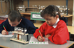 Primary school children recording results of experiment during biology lesson,