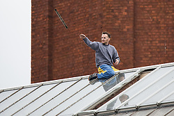 © Licensed to London News Pictures . 14/09/2015. Manchester, UK. STUART HORNER throws off strips off metal from the roof at HMP Manchester (formerly Strangeways Prison ) , where Horner is conducting a rooftop protest against prison conditions . Photo credit : Joel Goodman/LNP