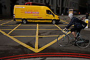 DHL delivery van turns mid-way over a yellow box junction grid with passing cyclist in a City of London street.