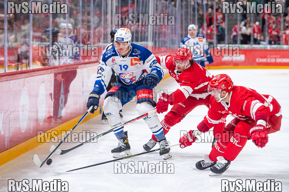 LAUSANNE, SWITZERLAND - OCTOBER 01: Reto Schappi #19 of ZSC Lions battles for the puck with Ken Jager #17 of Lausanne HC and Mark Barberio #44 of Lausanne HC during the Swiss National League game between Lausanne HC and ZSC Lions at Vaudoise Arena on October 1, 2021 in Lausanne, Switzerland. (Photo by Monika Majer/RvS.Media)