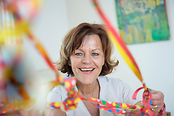 Portrait of senior woman with blowout paper streamer, smiling