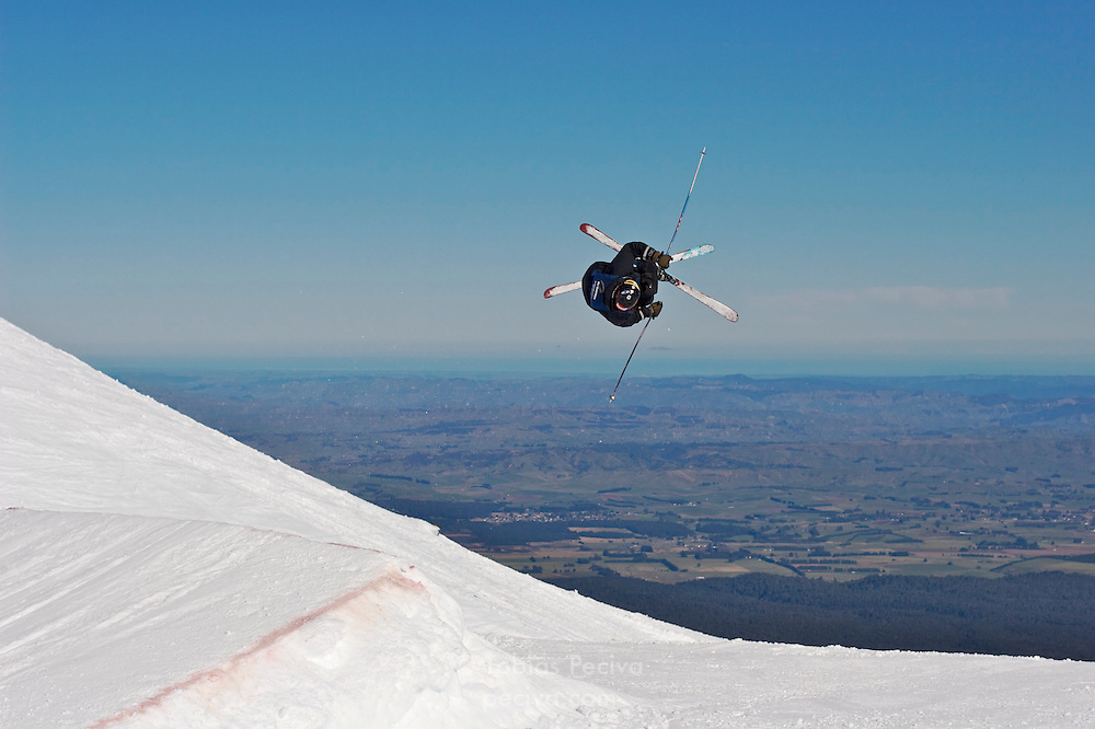 Skier performing an iron cross during a slopestyle competition at ski field Turoa. Turoa is located on active volcano Mount Ruapehu, New Zealand.