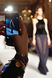 © Licensed to London News Pictures. 19/02/2016. Guest take a photo of a model on the catwalk with their camera phone at the PAUL COSTELLO Autumn/Winter 2016 presentation. Models, buyers, celebrities and the stylish descend upon London Fashion Week for the Autumn/Winters 2016 clothes collection shows. London, UK. Photo credit: Ray Tang/LNP