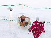 Following a sauna, a female ice swimmer waits while another gets out after a brief dip in a hole in the ice, Tuomiojarvi, Jyvaskyla, Central Finland. Ice swimming takes place in a body of water with a frozen crust of ice, which requires a hole cutting in it.  In Finland, the ice swimming tradition has generally been connected with the sauna tradition and it is not seen as an ascetic or religious ritual, but as a way to cool off rapidly after staying in the sauna and as a stress relief.