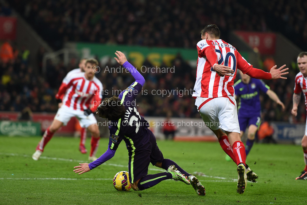 Geoff Cameron of Stoke city ® fouls David Silva of Manchester city and a penalty is awarded. Barclays Premier League match, Stoke city v Manchester city at the Britannia Stadium in Stoke on Trent , Staffs on Wed 11th Feb 2015.<br /> pic by Andrew Orchard, Andrew Orchard sports photography.
