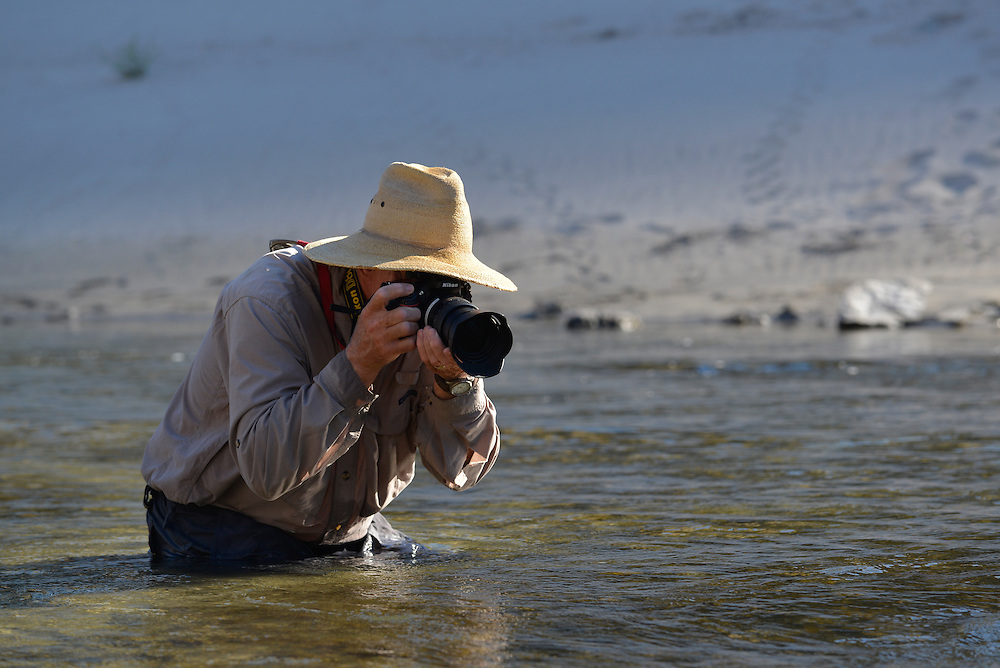 Photographer taking a picture while partially immersed in the Snake River, Hells Canyon, Oregon/Idaho.