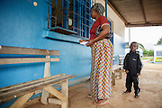 Katy Cherif, 40, waits to get prescription drugs for her twin sons Lusseini (not seen) and Lacine, both 4 and suffering from malaria and diarrhea, at the pharmacy counter of the Libreville health center in Man, Cote d'Ivoire on Wednesday July 24, 2013.