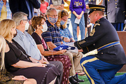 29 AUGUST 2020 - RUNNELLS, IOWA: The NCO In Charge of the Iowa Army National Guard Honor Guard presents the American flag to members of the family at the funeral for Pvt. Roy Brown Jr. in Runnells, IA. Pvt. Brown was a US Army soldier in World War II. He was an infantryman in the 126th Infantry Regiment, 32nd Infantry Division, serving in the Australian Territory of Papua (now Papua New Guinea). He went missing in action on Dec. 2, 1942. Unidentified remains were recovered on Feb. 2, 1943 and were eventually interred in the Manila American Cemetery. On May 14, 2019, Defense POW/MIA Accounting Agency using dental records, circumstantial evidence and DNA identified the remains as Pvt. Brown's. He was reinterred in the Lowman Cemetery in Runnells Saturday.     PHOTO BY JACK KURTZ