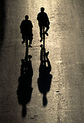 Two men riding bicycles down the road in silhouette