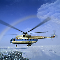 """Russian helicopter carries tourists for """"flight-seeing"""" tour at North Pole, under rainbow from airborne ice crystals over Arctic Ocean."""