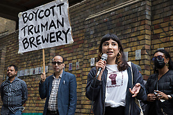 London, UK. 12th September, 2021. Javie Huxley of Save Latin Village addresses local residents and supporters of the Save Brick Lane campaign outside the Truman Brewery following a funeral procession along Brick Lane organised in protest against the ongoing gentrification of Shoreditch. Campaigners are protesting in particular against plans to develop the Truman Brewery into a shopping centre and 5-storey office building. Tower Hamlets experienced more gentrification than any other London borough between 2010-2016.
