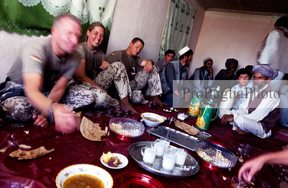 """YAFTAL PAYAN, 31 July 2005..German soldiers/ISAF having some food at Bitha Bala's guest house...They came here to meet the head of the village who, apparently, is not there...Ralph - on the left - says that their duty is to look at the life conditions of the villagers and to report it to the reconstruction team. ..""""The aim is to cooordinate the work of all NGOs operating in Afghanistan"""" he adds."""