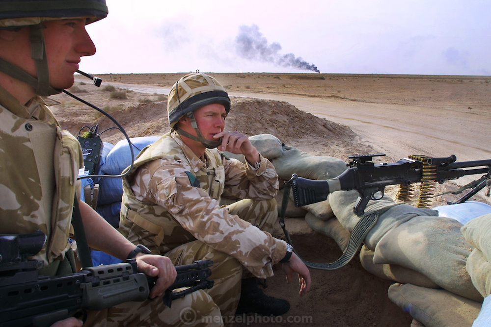 Paul Ross Muir and Philip Murray of the Royal Irish Regiment man a checkpoint that is part of the British effort to secure areas around burning oil wells in Iraq's Rumaila Oil Field, in southern Iraq. The wells were set on fire with explosives placed by retreating Iraqi troops when the US and UK invasion began. Seven or eight wells were set ablaze and at least one other was detonated but did not ignite. The Rumaila field is one of Iraq's biggest oil fields with five billion barrels in reserve. Rumaila is also spelled Rumeilah.