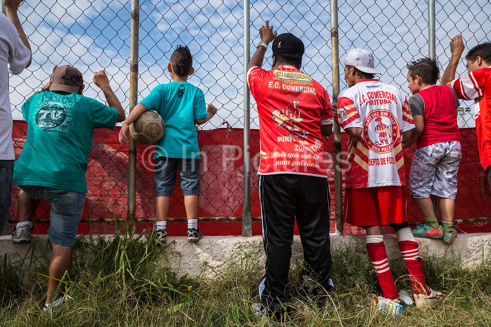 """Comercial FC Fans anxiously support their  amateur  football club's bid for the local state championship in a suburb of Sao Paulo city. """"Varzea"""" is the impassioned  amateur game supported by local businesses usually in poor neighbourhoods  of Brazil's large and small cities, 2013."""