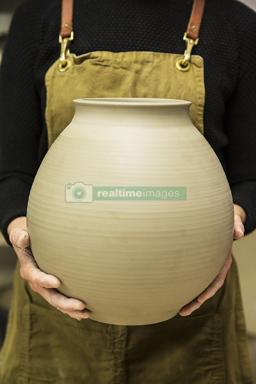 March 1, 2018 - Close up of potter wearing apron holding unfired spherical clay vase. (Credit Image: © Mint Images via ZUMA Wire)