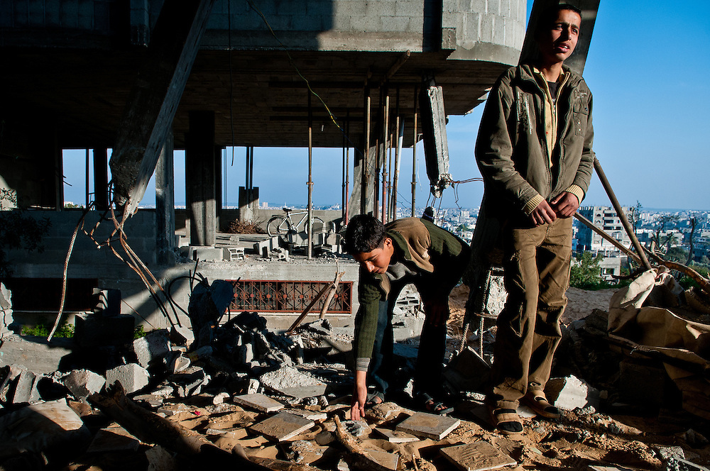 Boys stand in the wreckage of their family home in Beit Lahia.