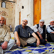 Elderly men waiting for time of prayer protected from mid day sun