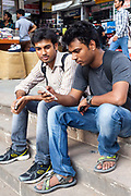 Young people connecting on their mobile telephones at the market in Nehru Place Nehru Place is a commercial hub in South Delhi that is dominated by electrical and computer and technology shops and New Delhi, India